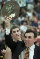 McQuaid coach Joe Marchese holds up the team trophy after McQuaid's win over Bennett High School in their state quarterfinal game Saturday, March 9, 2002 at Buffalo State College. McQuaid won the game 72-41 to move on to the state semifinals in Glens Falls.
