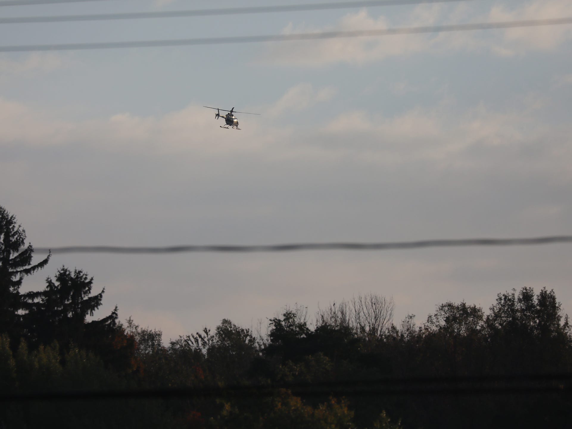 A New York State Police helicopter searches the area near the shooting for the suspect Tuesday, Oct. 23, 2018.