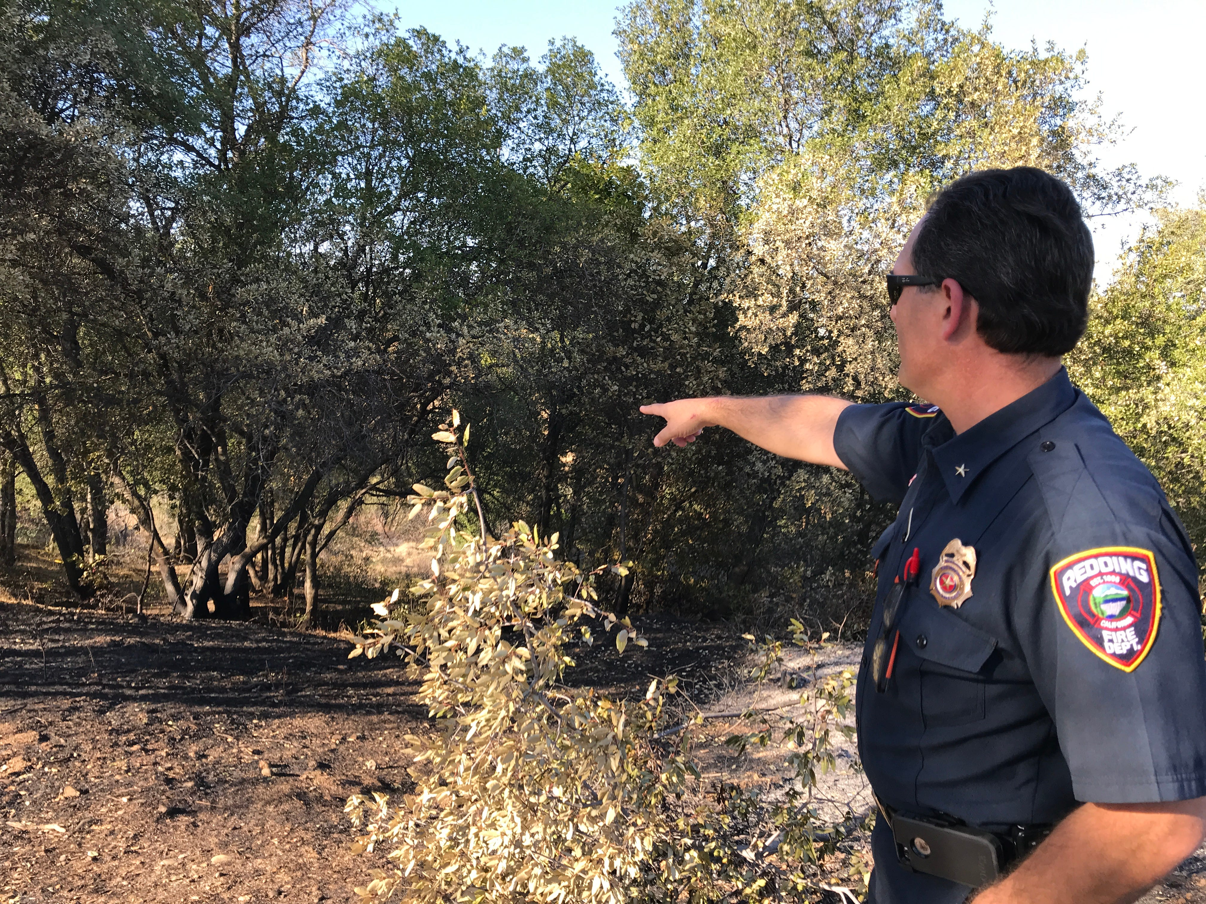 Redding Fire Marshal Craig Wittner points to the area where the Oct. 14, 2018 Masonic Fire burned in the Sulphur Creek Canyon in north Redding. The human-caused fire started on private property before it crossed into city-owned property and eventually burned a home. Wittner said a brush-clearing project two years ago saved more homes from burning.