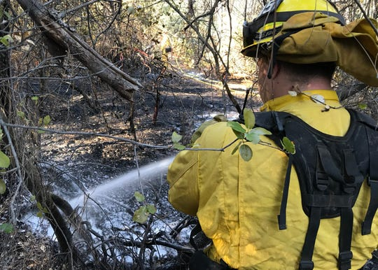 Redding firefighters mop up at a fire off Keswick Dam Road in Redding on Monday.
