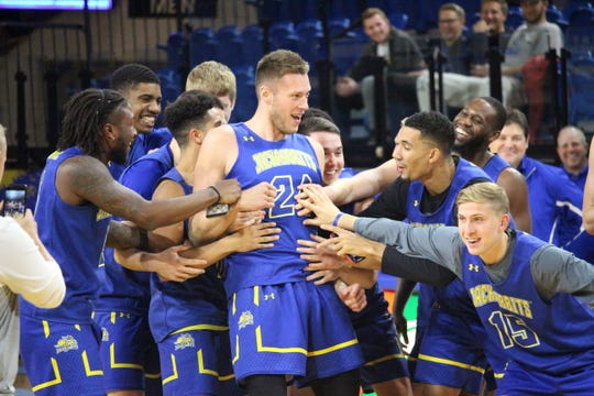 Mike Daum celebrates with teammates after winning the 3-point contest at the Jackrabbit tipoff last week at Frost Arena
