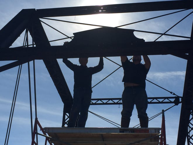 Silhouetted by the noon sun, Mark Benedict, right, and Teddy McCarty, road and bridge foreman, left, install the original sign identifying the builders of the bridge as the Wrought Iron Bridge Company. The sign was left off the 1891 bridge when it was moved in the 1930s.