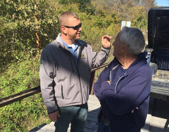 Hickory County Commissioner Chase Crawford talks about the importance of the Rough Holler Bridge with neighbor Mike Bobbitt, who attended the installation of the builders' sign.