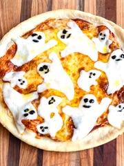 Mozzarella ghosts top tasty Halloween pizza.