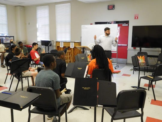 Lee Commander introduces his students to a new piece of music while they keep a steady beat.
