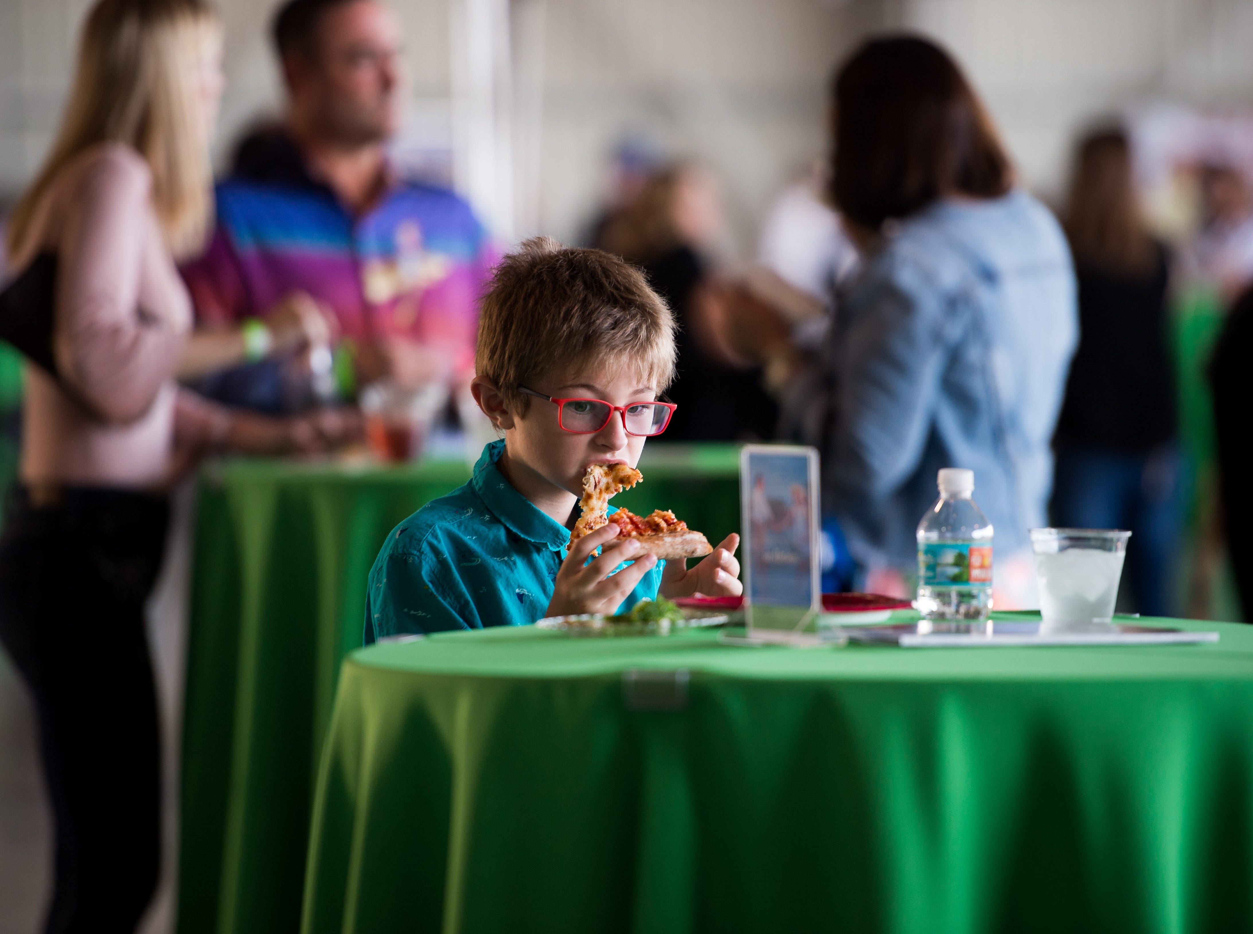 Zackery Lowe, 8, of Port St. Lucie, takes in a bite of pizza at the Big Taste of Martin County on Tuesday, Oct. 23, 2018, at the Stuart Jet Center in Stuart. Zackery was attending the event with his father, Richard Lowe with sponsor Southern Eagle Distributing.