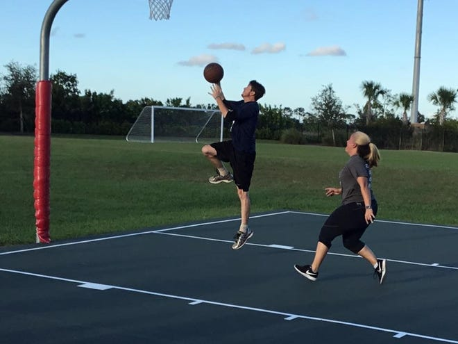 Sixth grade science teacher Charles Cooke from Renaissance Charter School St Lucie goes for a basket against Renaissance Charter School of Tradition's first grade teacher Courtney Council.