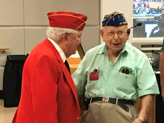"""World War II veterans Joe Hiott, 95, and Israel """"Ralph"""" Schulman, 96, chat after a ceremony honoring Purple Heart medal recipients on Oct. 22, 2018 in the Port St. Lucie City Council Chamber."""