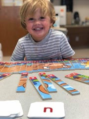 In a private lesson at Vero Reading Garden, a preschool student works on an ABC puzzle as he follows his teacher's lead with letter cards.