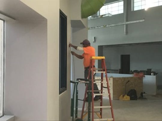 A worker installing wiring on Oct. 23, 2018 inside the new St. Lucie County Tax Collector's Office in Tradition.