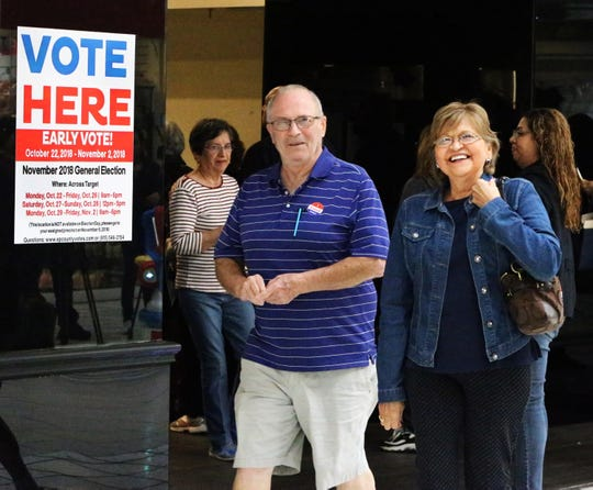 "Daniel and Soledad Mooneyhan walk out of the early polling station inside Bassett Place on Oct. 23 during the second day of early voting for the Nov. 6 midterm election. Always one of the most frequented early polling locations, the site saw 1,500 people vote on the first day, Oct. 22, a polling station judge there said. Daniel Mooneyhan said they went there ""because it's going to be crowded on Nov. 6, so we come today."""