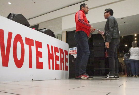 Carlos Lopez, center, went to the early polling station inside Bassett Place to cast his ballot during the second day of early voting Tuesday.