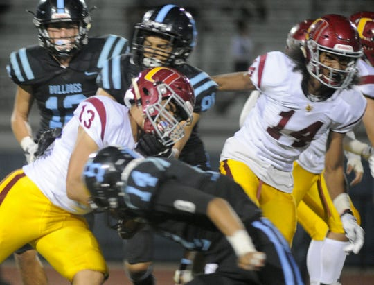 Oxnard's Nick Sanchez runs the ball against Buena High School's Abraham Friend. Officials and coaches say changes in the game reduce but can't eliminate the chance of injury.
