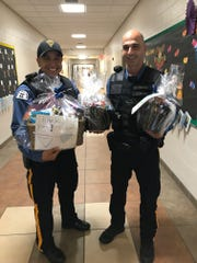 """Vineland Police officers Edmanuel Vega (left) and Lou Rivera are all smiles as they accept """"baskets of kindness"""" from the Petway Patriots."""