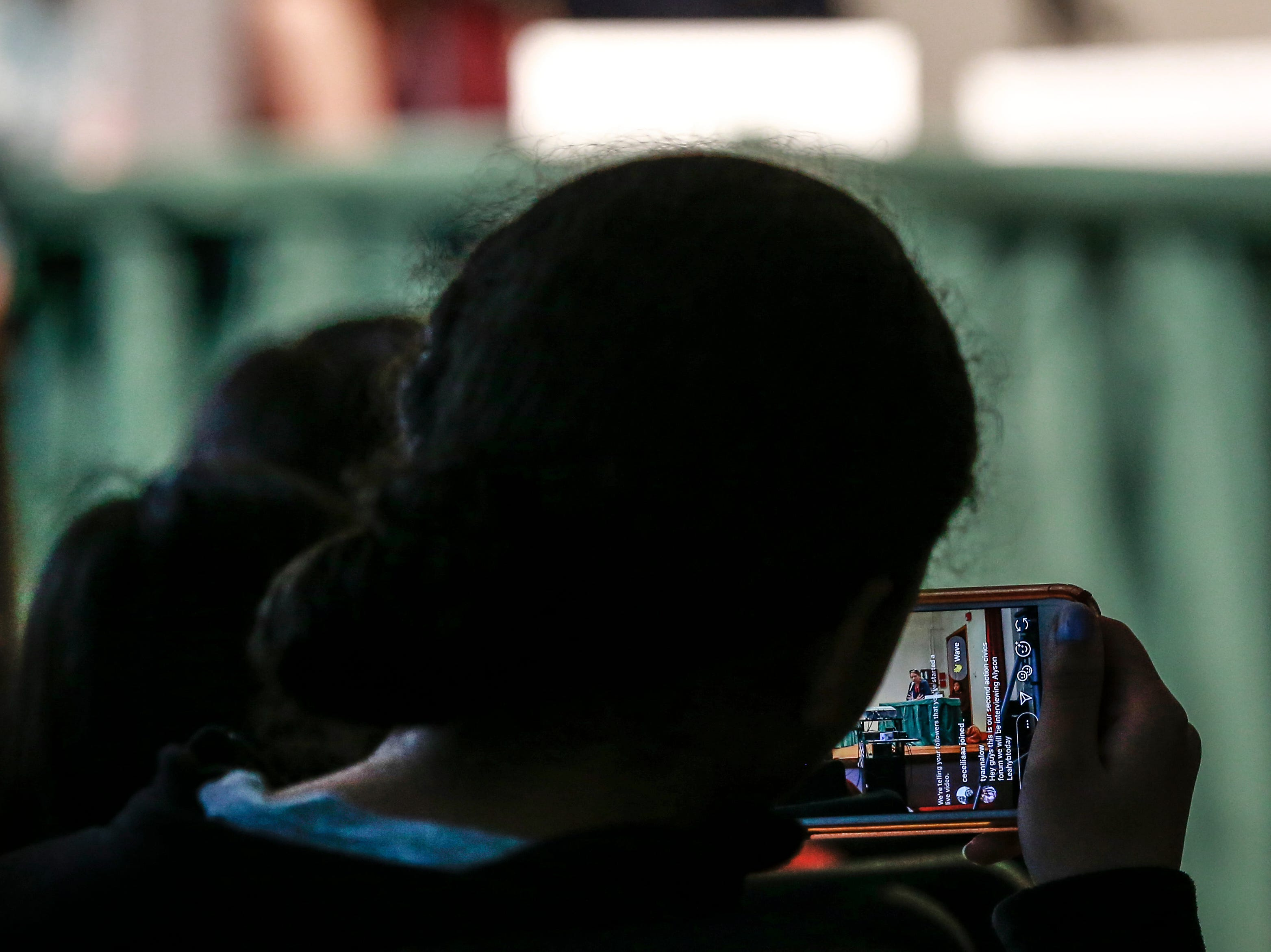 A student Facebook lives during the 9th grade Action Civics Political Forum Wednesday, Oct. 17, 2018, at D.C. Everest Junior High School auditorium in Weston, Wis. T'xer Zhon Kha/USA TODAY NETWORK-Wisconsin