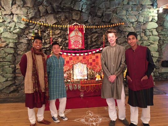 Nikhiel Biswas, Elkin Thao, Isaac Westberg and Neil Biswas stand in front of a Hindu shrine at a past Diwali celebration.