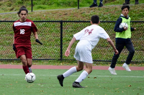 Ossining midfielder Eric Monges looks for room away from the sideline Monday in the second half of a 1-0 playoff win over Scarsdale and defender Ben Rubin.