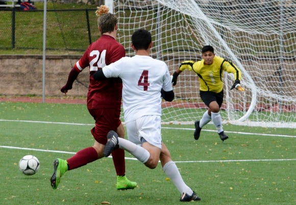 Ossining center back Sebastian Tejera runs Scarsdale's Nico Bernard off the ball, allowing Pride goalie Carlos Zabarburu pick up the ball without pressure during the first half Monday.