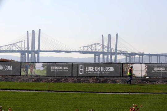 A worker walks past banners for the Edge-on-Hudson, a new residential development planned for the site of the former General Motors assembly plant in Sleepy Hollow Oct. 23, 2018. Construction of townhomes at the site has begun. Infrastructure work, the planting of grass, as well as pile driving for foundations is under way.