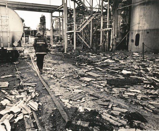 A firefighter walks through rubble from an explosion at an Amoco chemical plant on Oct. 22, 1980.