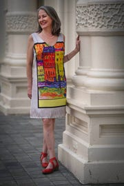 Lucy Clemens wears a silver gray dress with an image of brightly colored painting in a black border, by Sweet Miss, with Fly of London Piat Devil red pumps.