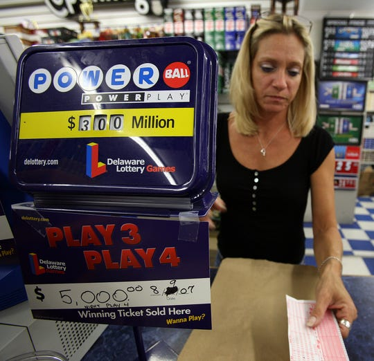 Bev Ward, a store clerk at Airport News in New Castle, sells Powerball lottery in this file photo. Wednesday's jackpot is worth nearly $400 million.