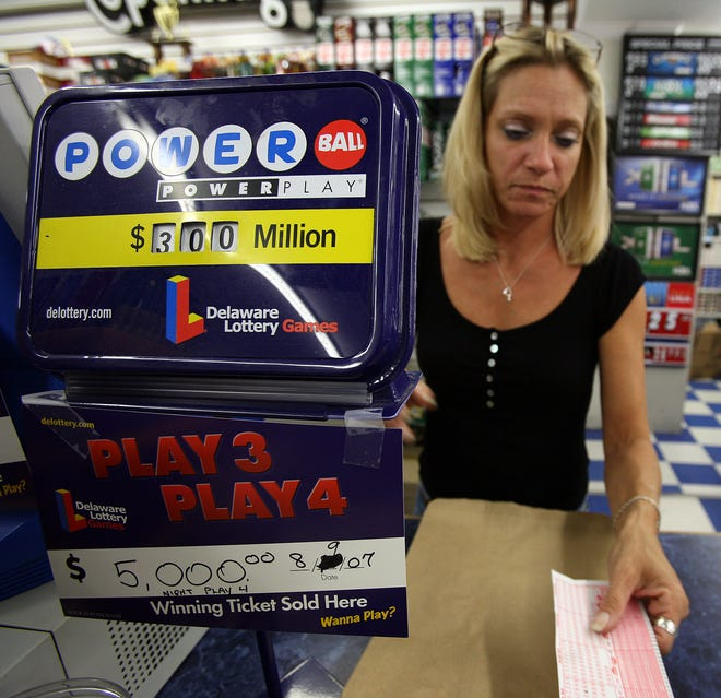 Bev Ward, a store clerk at Airport News in New Castle, sells Powerball lottery tickets. The new estimated jackpot is at $750 million after Wednesday night's drawing.