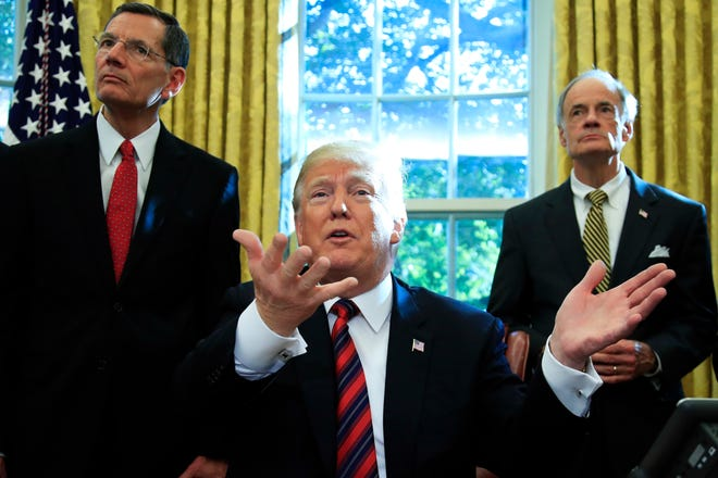"""How uncomfortable is he? Delaware Sen. Tom Carper stands behind President Donald Trump as he takes questions from reporters after signing the """"America's Water Infrastructure Act of 2018"""" into law in the Oval Office at the White House in Washington, Tuesday, Oct. 23, 2018."""