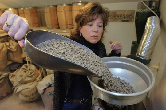 Carol Allston-Stiles fills a coffee roaster with five pounds of Arabican beans.  She and her husband Peter who own Pike Creek Coffee Roasters are selling the business they founded in 2006.