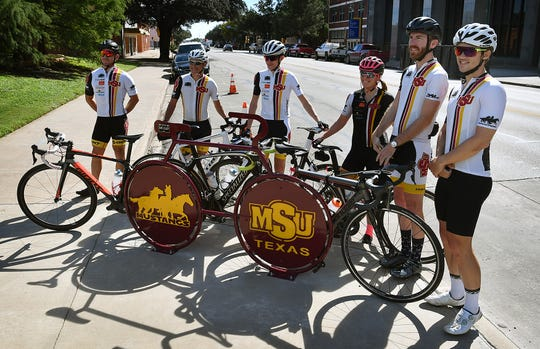 Members of the Midwestern State University Cycling Team are photographed around the new downtown bike rack at Scott Avenue and 8th Street Tuesday.