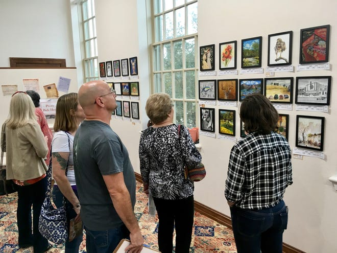 In this file photo, attendees to the Kemp Center for the Arts Mystery Art Fest bid on their favorite works, without knowing the artists. The annual exhibit will be Oct. 25. Artwork entry deadline is 5 p.m. Sept. 4.