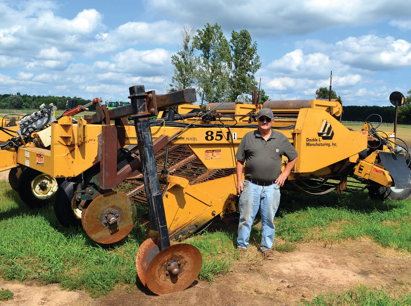 Gary stands beside one of the farm's windrower machines that goes in front of the potato harvester.
