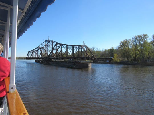 A swing railroad bridge opens to allow for the passage of the riverboat LaCrosse Queen.