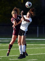 Cora Wilkins, left, goes up for a heade during John Glenn's 3-1 win against New Philadelphia in a Division II district semifinal on Monday in Coshocton.