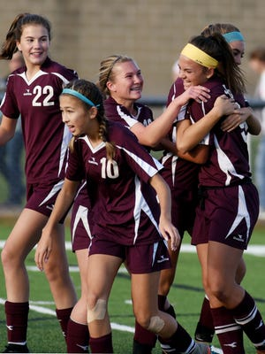 Teammates celebrate with Gabby Lemon, right, after she scored a goal in the first half of John Glenn's 3-1 win against New Philadelphia in a Division II district semifinal on Monday in Coshocton.