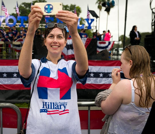 London resident Eve Byrne takes a selfie in front of a stage where Hillary Clinton appeared at a Pembroke Pines, Fla. campaign rally on Saturday, Nov. 5, 2016. The logo on her T-shirt was designed by Michael Bierut and his team at Pentagram.