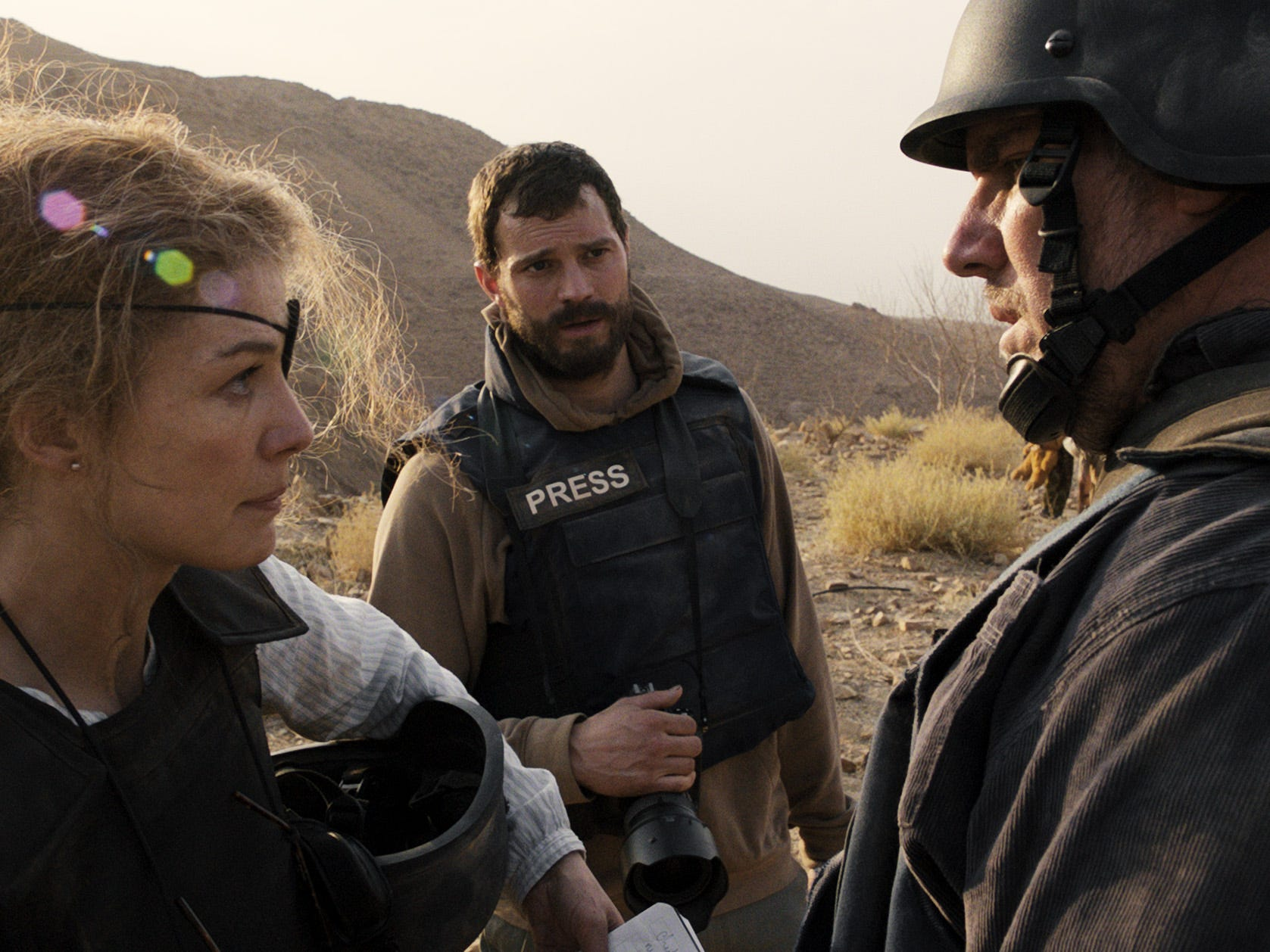 "War correspondent Marie Colvin (Rosamund Pike, far left) and photographer Paul Conroy (Jamie Dornan) go wherever in the world there's a story in ""A Private War."""