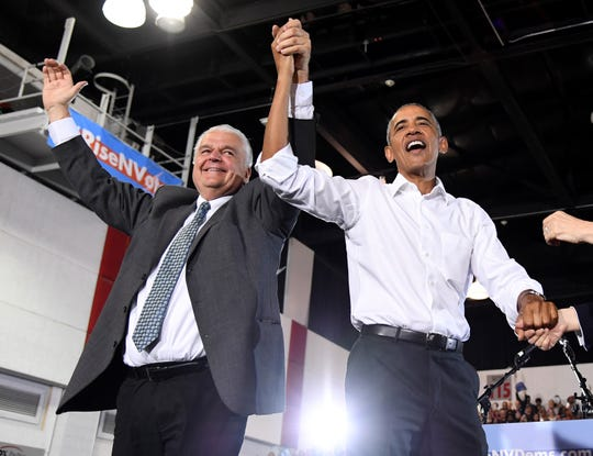 Clark County Commission Chairman and Democratic gubernatorial candidate Steve Sisolak, left, and former President Barack Obama hold hands and raise their arms after speaking at a get-out-the-vote rally at the Cox Pavilion as Obama campaigns for Nevada Democratic candidates Oct. 22, 2018, in Las Vegas.