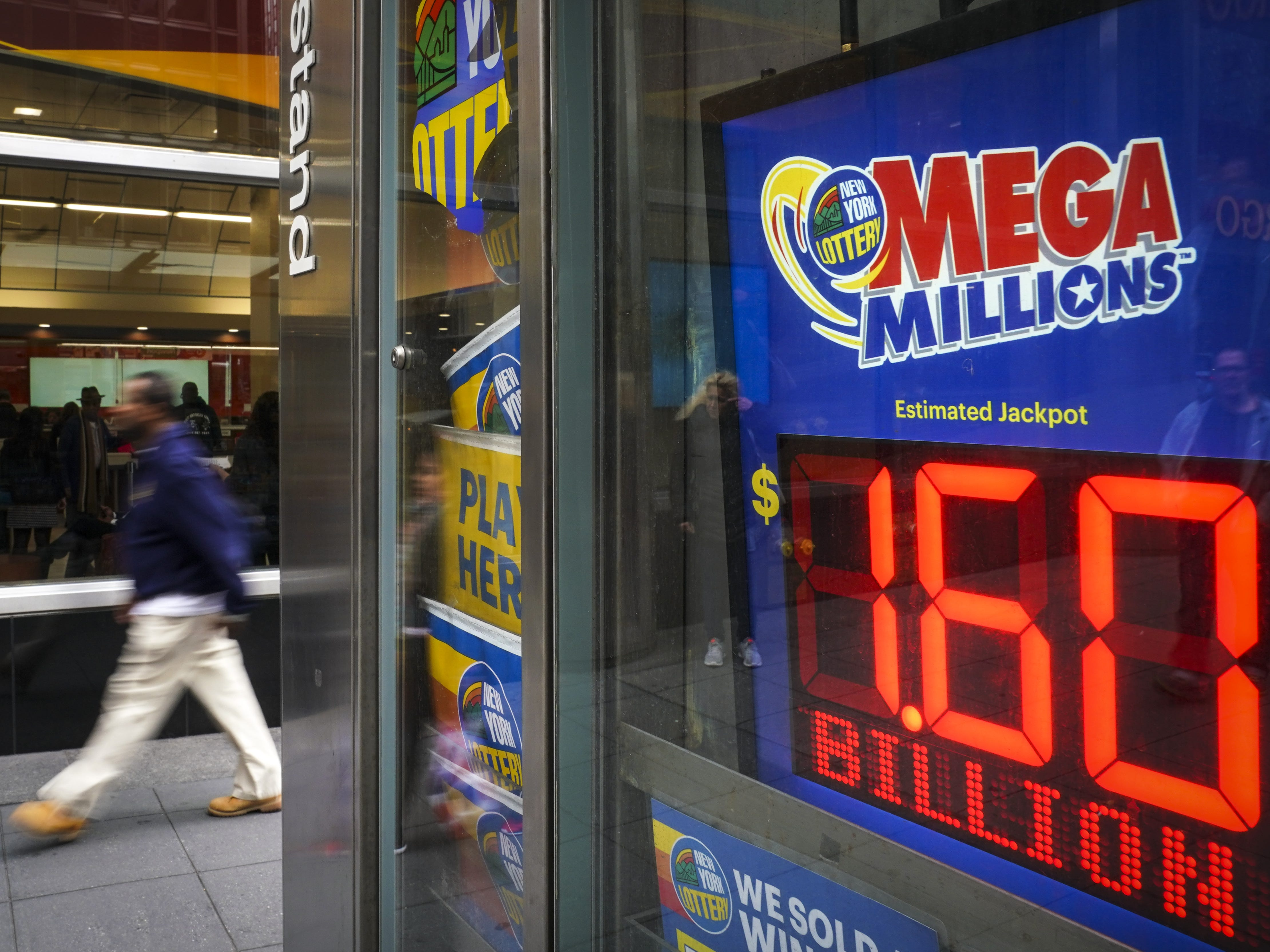 A person walks past a newsstand with advertisements for the Mega Millions lottery, Oct. 23, 2018 in New York.