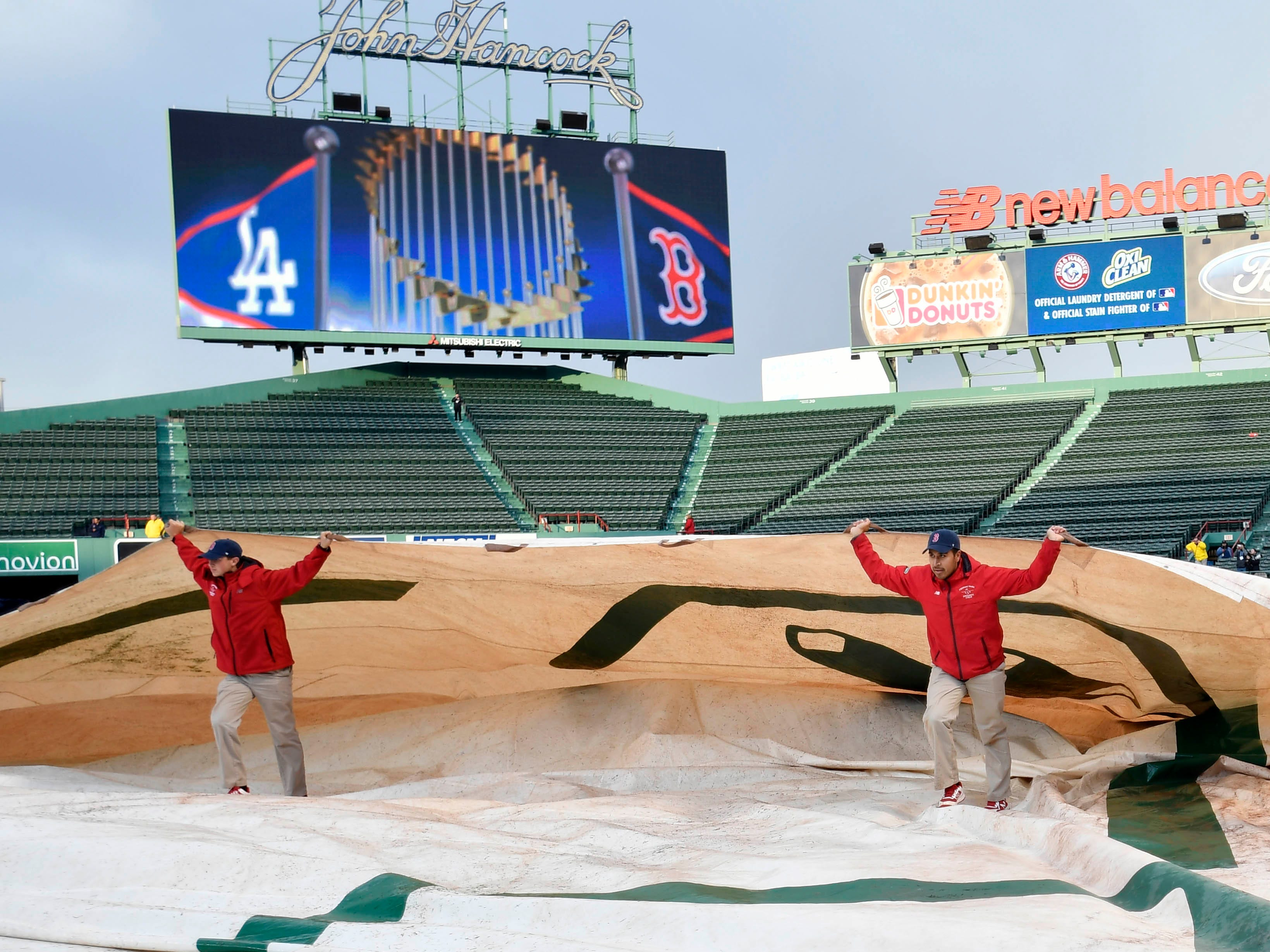 Game 1 at Fenway Park: The grounds crew removes the tarp from the field.