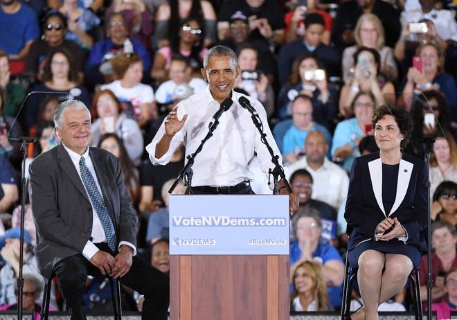 Former President Barack Obama speaks as Clark County Commission Chairman and Democratic gubernatorial candidate Steve Sisolak, left, and U.S. Rep. and U.S. Senate candidate Jacky Rosen, D-Nev.,  look on during a get-out-the-vote rally at the Cox Pavilion in Las Vegas Oct. 22, 2018.