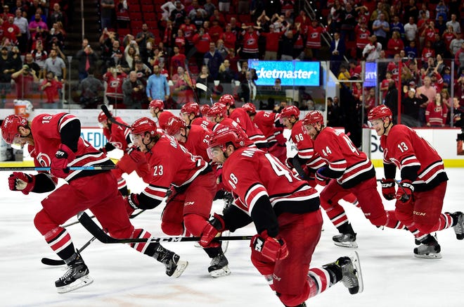Hurricanes players charge across the ice to greet fans after a win over the Canucks at PNC Arena on October 9, 2018.