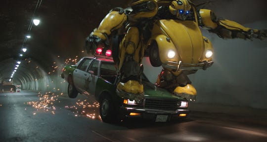 """Bumblebee takes out a police car while in mid-transformation in the 1980s-set """"Transformers"""" spinoff """"Bumblebee."""""""