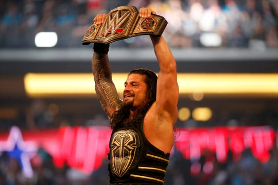 Roman Reigns holds up the championship belt after defeating Triple H during WrestleMania 32.