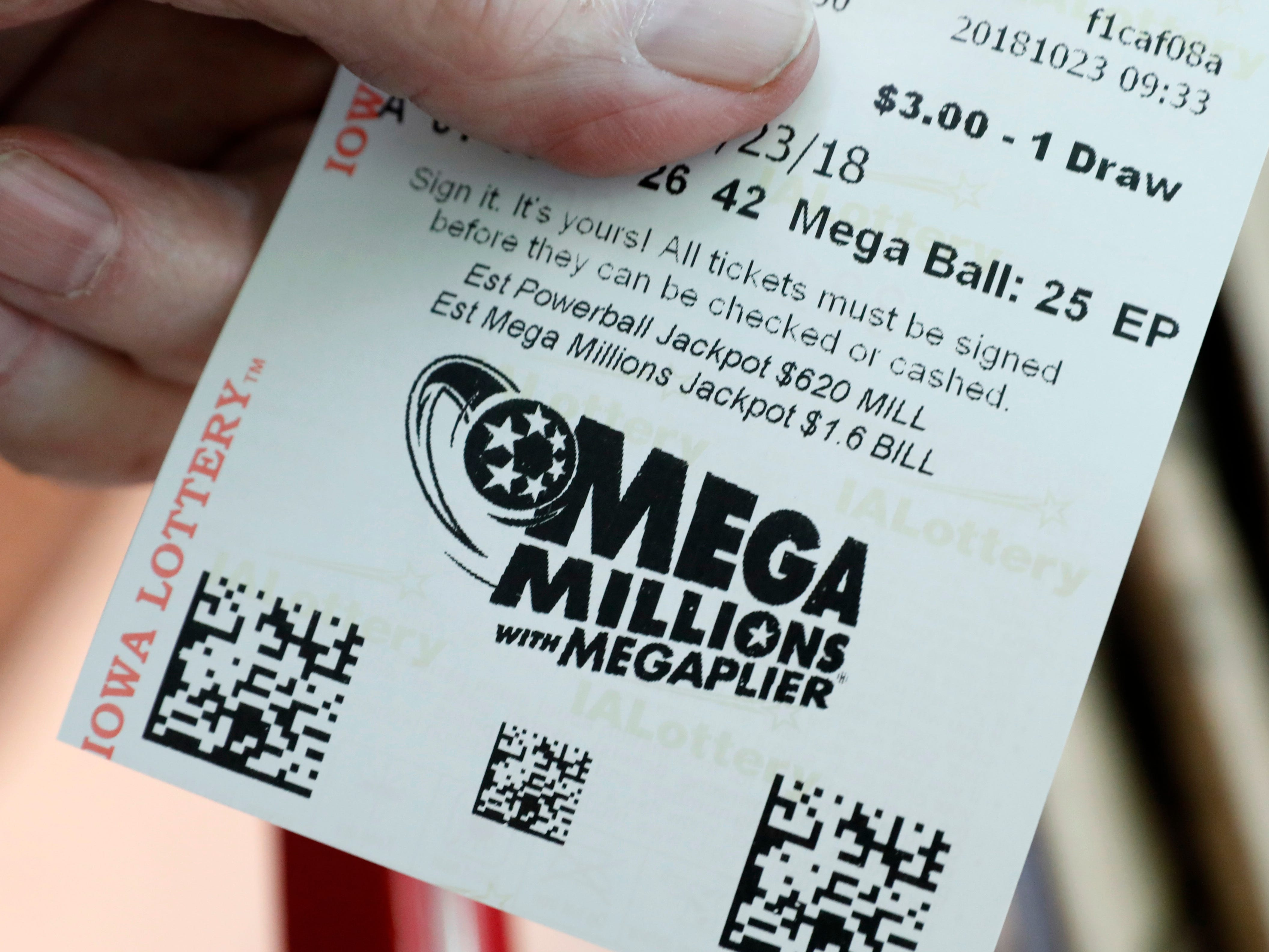 A customer shows his Mega Millions lottery ticket at a local grocery store, Tuesday, Oct. 23, 2018, in Des Moines, Iowa.