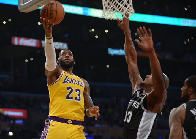 Los Angeles Lakers forward LeBron James moves to the basket against the defense of San Antonio Spurs forward Dante Cunningham during the first half at Staples Center.