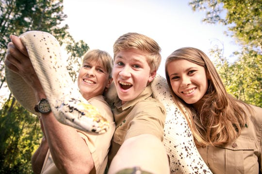 Terri, left, Robert and Bindi Irwin pose for a selfie with a snake at the Australia Zoo.
