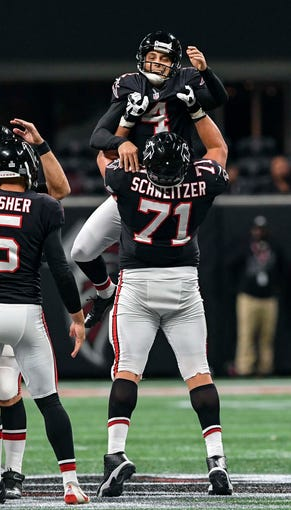 Atlanta Falcons kicker Giorgio Tavecchio reacts with offensive guard Wes Schweitzer (71) after kicking a 56-yard field goal against the New York Giants during the fourth quarter at Mercedes-Benz Stadium.