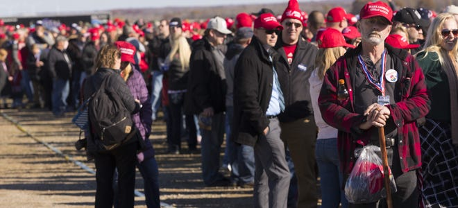 Hats are among the souvenirs offered for sale to the thousands of people lined up Wednesday hours before President Trump is scheduled to speak at a rally at Central Wisconsin Airport in Mosinee.