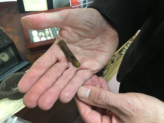 Rev. Frank Watson holds a nail, fused to wood, from the coffin of murdered Duffy's Cut laborer John Ruddy.